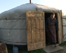 Mongolian nomad exits enters yurt Stock Footage