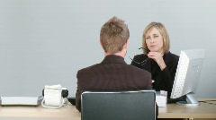 Two associates talking on a desk Stock Footage
