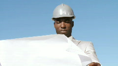 Well organised architect with a helmetv looking on a blueprint Stock Footage