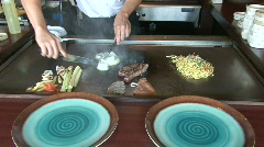 Hibachi chef cooks meat Stock Footage