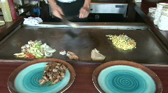 Hibachi chef cooks noodles Stock Footage