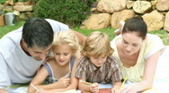 Parents with their children in the garden painting Stock Footage