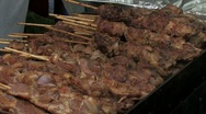 Grilling steak on a stick on a barbeque Stock Footage