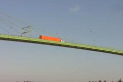 Orange truck crosses green bridge. Tracking shot. Stock Footage