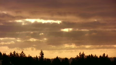 Time lapse of clouds rolling by at sunrise with rays of light. - stock footage
