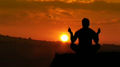 Man meditating at Sunset Stock Footage