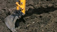 Excavator bucket digging earthworks on a building site. - stock footage