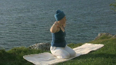Woman doing Kundalini yoga on a cliff next to the ocean Stock Footage