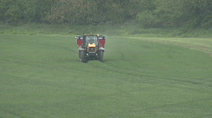 Tractor spraying fertiliser pellets sends up a bird Stock Footage