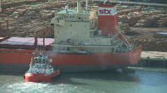 tug pushes log ship into berth - stock footage