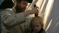 First haircut at Hasidic celebration of Lag B'omer in Meron Stock Footage