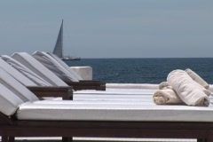 Hotel terrasse with white empty sunloungers. Blue sea in background. Stock Footage