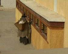 Old woman rotating turning praying wheels in monastery  Stock Footage