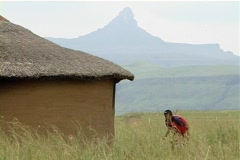 Kids playing outside African mud hut Stock Footage