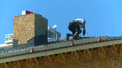 Roofer shingling roof Stock Footage