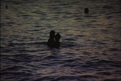 Couple Play in the Surf at Dusk Stock Footage