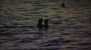 Stock Video Footage of Couple Play in the Surf at Dusk