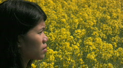 Asian woman with a flowering canola field in the background - stock footage