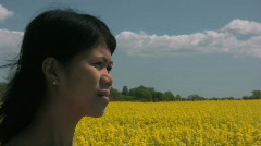 Asian woman with a flowering canola field in the background Stock Footage