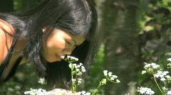 Asian woman smelling summer wildflowers cow parsley Stock Footage