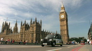 Stock Video Footage of Black cab & red bus passing Big Ben and the Houses of Parliament London England