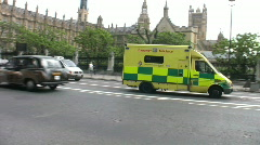 Emergency ambulance passing the Houses of Parliament London England UK Stock Footage