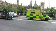 Stock Video Footage of Emergency ambulance passing the Houses of Parliament London England UK