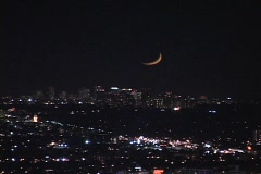 A sliver of moon hangs low in the night sky. Stock Footage