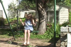A girl swings in front of small cottage. Stock Footage