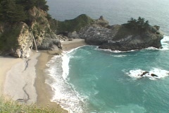 A gentle waterfall spills onto the sandy shore along the rugged Big Sur Stock Footage