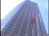 An American flag waves in the wind in front of a skyscraper. Stock Footage