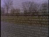 Stock Video Footage of The Vietnam War Memorial reflects the image of a man.
