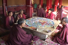 Buddhist monks sit and chant around a mandala. Stock Footage