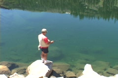 A fisherman fishes in high Sierra Lake. Stock Footage