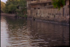 Buildings line a canal near a temple in Bangkok, Thailand. Stock Footage