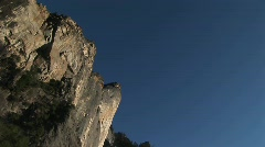 The camera pans left across vertical cliffs to a cascading waterfall Stock Footage