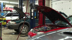 Medium-shot of cars in a repair shop. Stock Footage