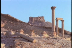 Roman style pillars stand in partial ruin in a desert. Stock Footage