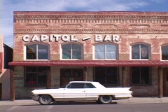 A vintage Cadillac stands parked in front of the Capitol Bar. Stock Footage