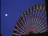 A ferries wheel turns in an amusement park. Stock Footage