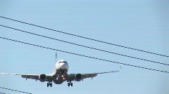 An airplane flies over power lines with its landing gear down Stock Footage