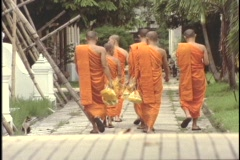 Buddhist monks slowly stroll through the monastery. Stock Footage