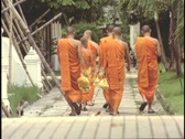 Stock Video Footage of Buddhist monks slowly stroll through the monastery.