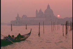 A gondolier guides a gondola across the sea approaching Venice at golden hour. Stock Footage