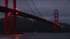 Golden Gate Bridge at night with its lights reflecting on the water - stock footage