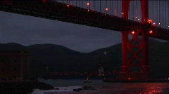 Small boats passing under the Golden Gate Bridge at night Stock Footage