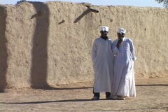 Sudanese men wear kaftans  in front of a stone wall. Stock Footage