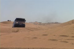 A race car races over hills in the desert Stock Footage