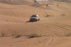 A race car races over hills in the desert. Stock Footage