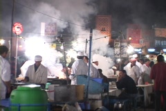 Steam rises as chefs cook outside on a busy city street. Stock Footage